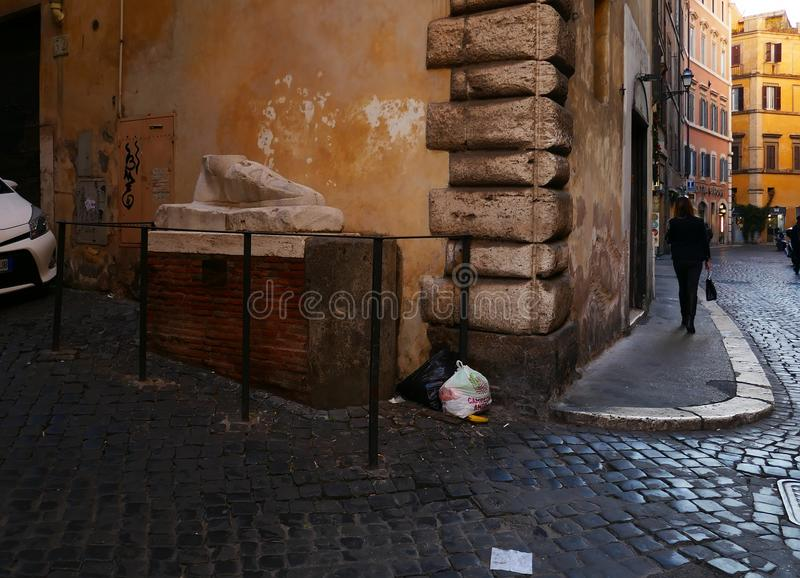 Pie` di Marmo garbage under ancient Roman Monument. ROME, ITALY - DECEMBER 6, 2017: Trash left under the Ancient giant marble foot part of a Roman monument in royalty free stock photos