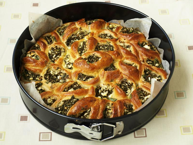 Pie with feta and spinach in the form of separate pies after baking, horizontal orientation. Close up stock image