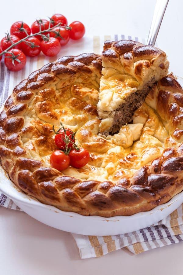 Pie met vlees en tomaten in een witte bakschaal stock afbeeldingen