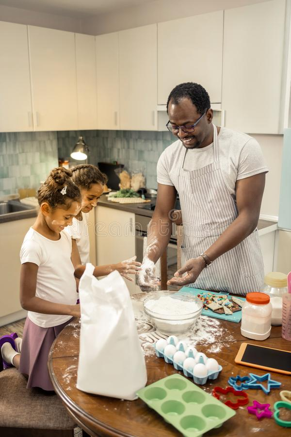 Father and daughters feeling amazing cooking pie for mother together. Pie for mother. Father and cute little daughters feeling amazing cooking pie for mother stock photos