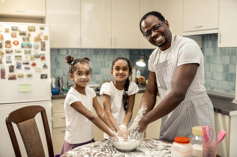 Father in striped apron and two cute daughters cooking pie for mother. Pie for mother. Father in striped apron and two cute daughters cooking pie for mother at stock image