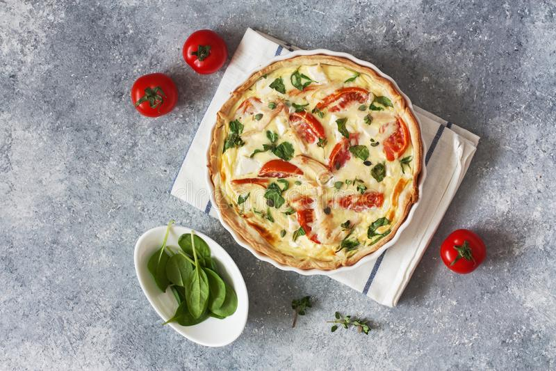 Pie quiche with chicken, spinach and tomatoes. Chicken, spinach and tomatoes pie quiche on a blue stone background. Top view royalty free stock photos