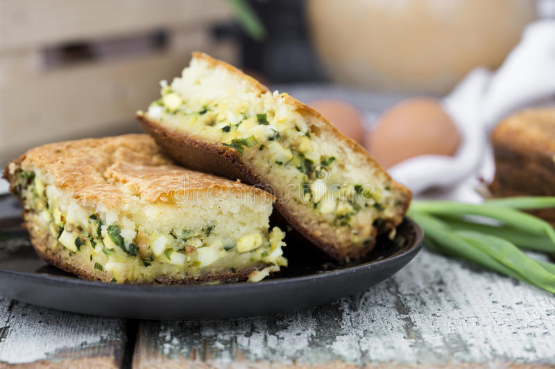 Pie with spring onion and eggs. On the table stock photos
