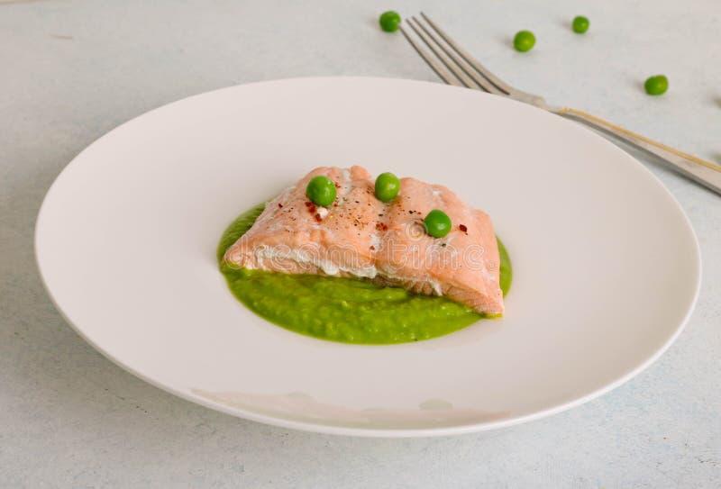 Piec łososiowy stek z sezamowymi ziarnami i słuzyć z mashed zielonymi grochami zdjęcia stock