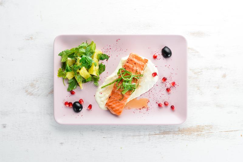 Piec łosoś polędwicowy z warzywami na talerzu Na drewnianym tle obraz royalty free