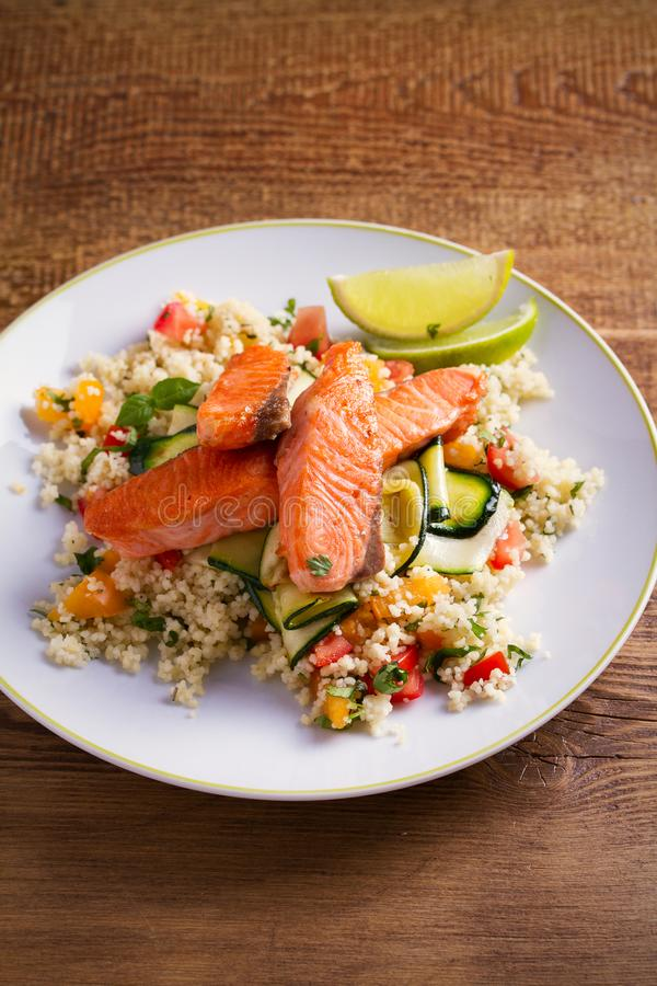 Piec łosoś ryba z pomidorowym couscous, zucchini i wapnem na bielu talerzu, zdjęcie stock