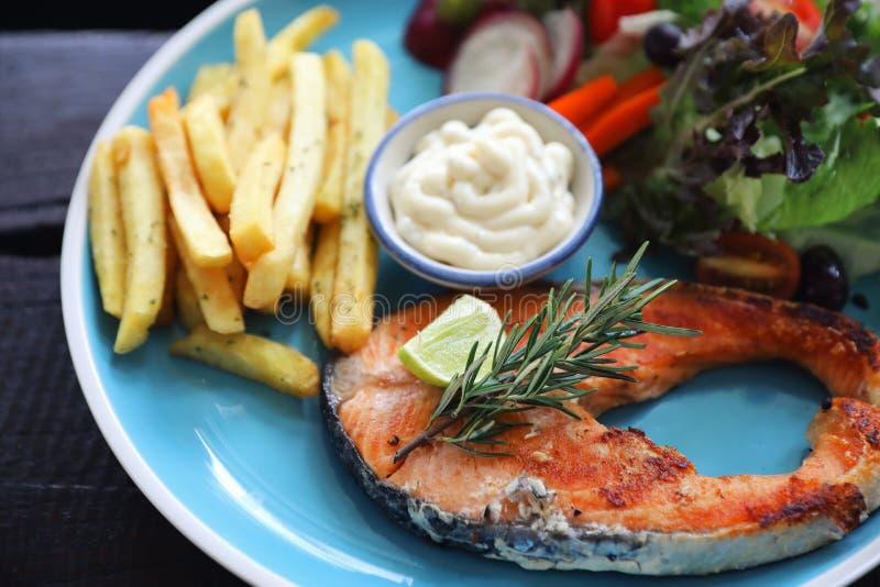 Piec łososiowy stek, piec łosoś z sałatkowym świeżym warzywem na drewnianym stole fotografia stock