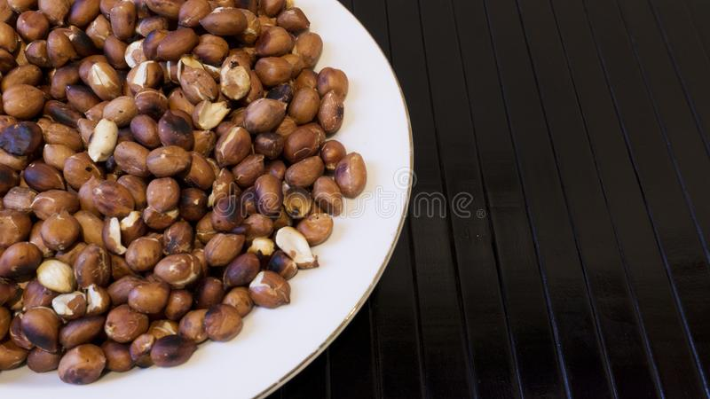 Piec arachidy Przekąszają w bielu talerzu w Drewnianych tło - Тopview ans zbliżenie fotografia royalty free