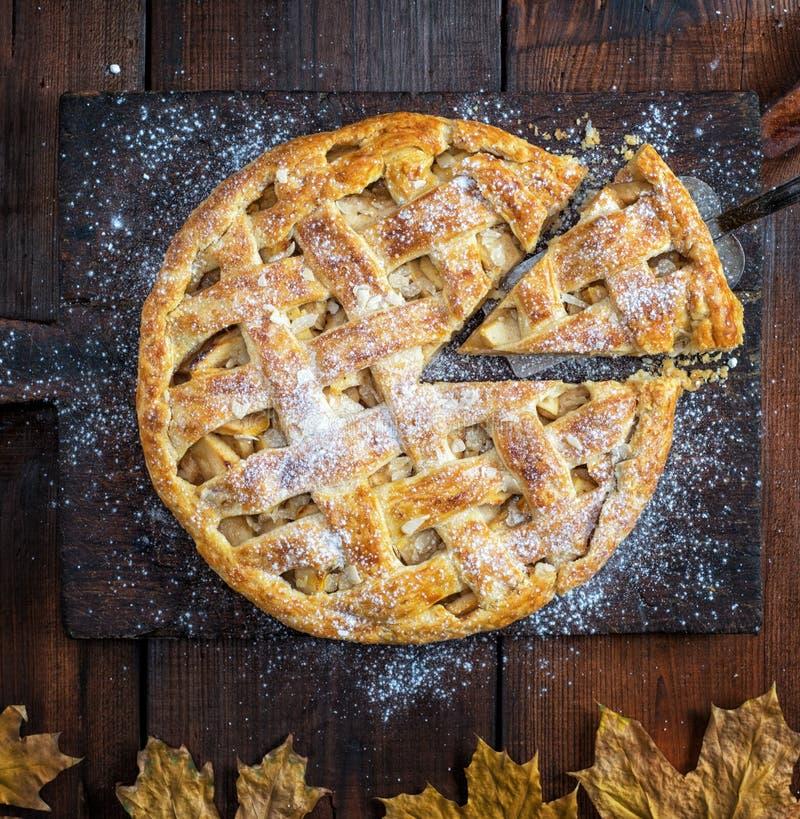 Piec całego round jabłczany kulebiak na prostokątnego starego brązu tnącej desce kropiącej z sproszkowanym cukierem obrazy stock