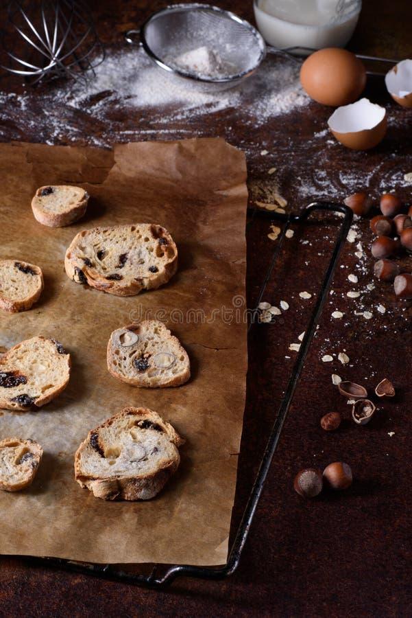Piec chlebowi rusks z rodzynkami i dokrętkami, kulinarni składniki nad nieociosanym kuchennym stołem Hazelnut ciastka, crispy app zdjęcia royalty free