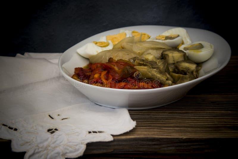 Piec czerwoni pieprze, s?odkie cebule, aubergines i gotuj?cy si? jajka na drewnianym tle, obraz stock