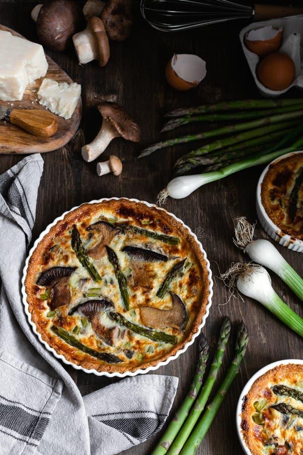 Piec domowej roboty quiche kulebiak z asparagusem i pieczarkami w białej ceramicznej formie na drewnianym tle, mieszkanie nieatut zdjęcia royalty free