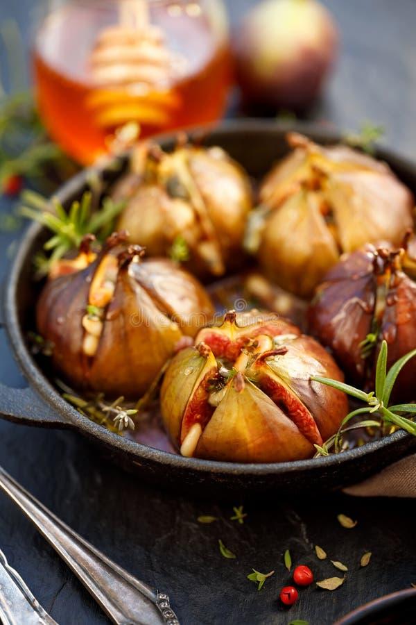 Piec figi faszerować z Gorgonzola serem, sosnowymi dokrętkami, miodem i ziele w czarnym naczyniu na zmroku, kamienny tło, odgórny obrazy royalty free