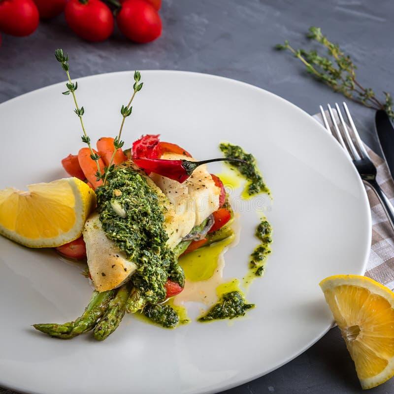 Piec halibuta rybi stek z cytryny, marchewki i kumberlandu salsa verde, Bielu talerz, macierzanka, łyżka, rozwidlenie na popielat zdjęcie royalty free
