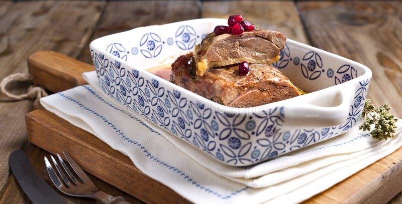 Piec kaczka polędwicowa z granatowiec jagodami w ceramicznej wypiekowej tacy z wzorami na drewnianym stole Jedzenie dla zdrowego  zdjęcia royalty free