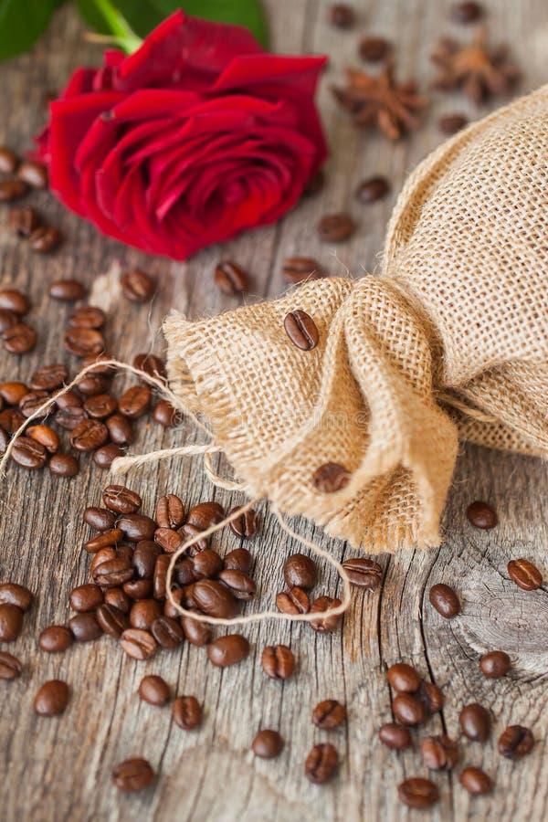 Piec kawowe fasole na brown drewnianym tle z prostackim z grubsza wyplatającym burlap i czerwieni różą, grunge tekstura wierzchoł obraz royalty free