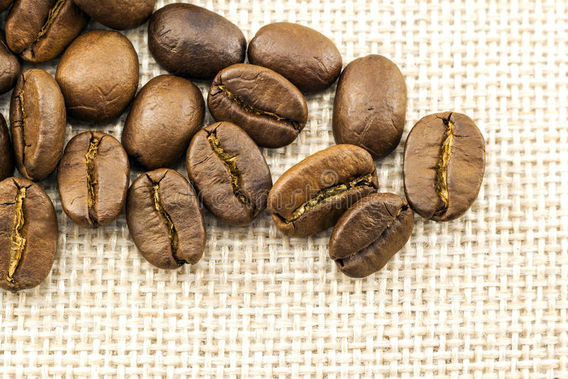 Piec kawowe fasole na burlap tekstury parcianym tle zdjęcia stock