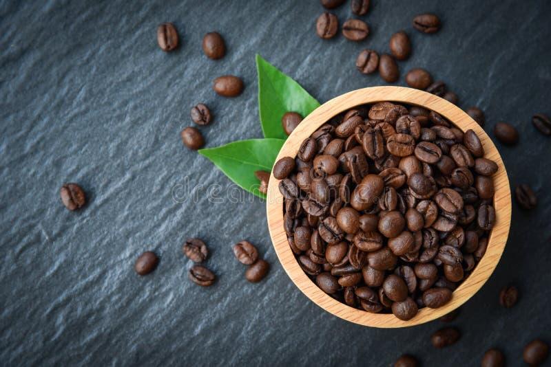 Piec kawowe fasole na drewnianym pucharze zielenieją liść i zmroku tło - odgórny widok fotografia stock
