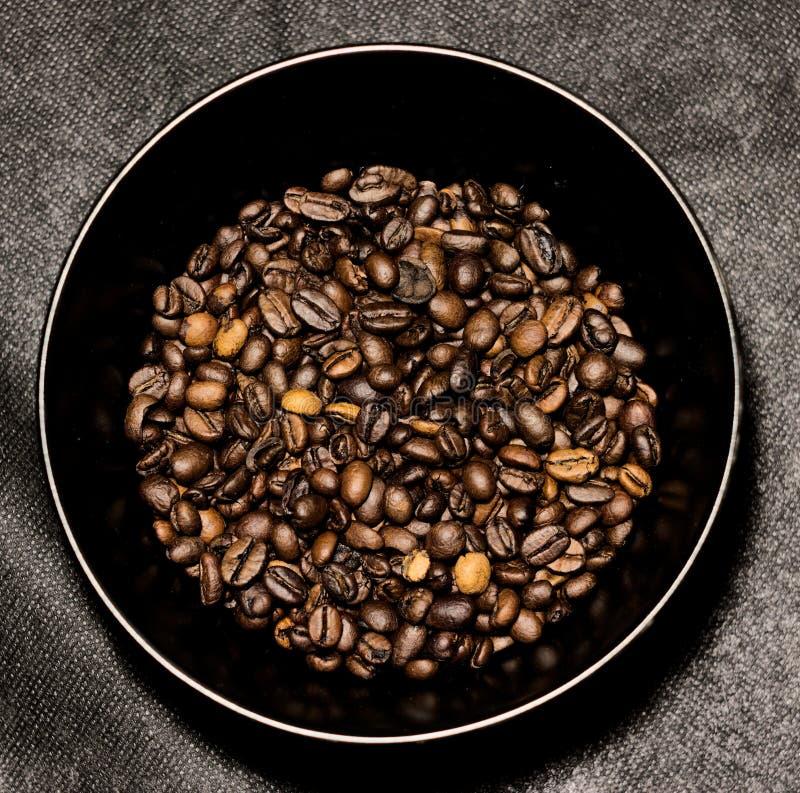 Piec kawowe fasole w czarnej filiżance na darck tle fotografia stock