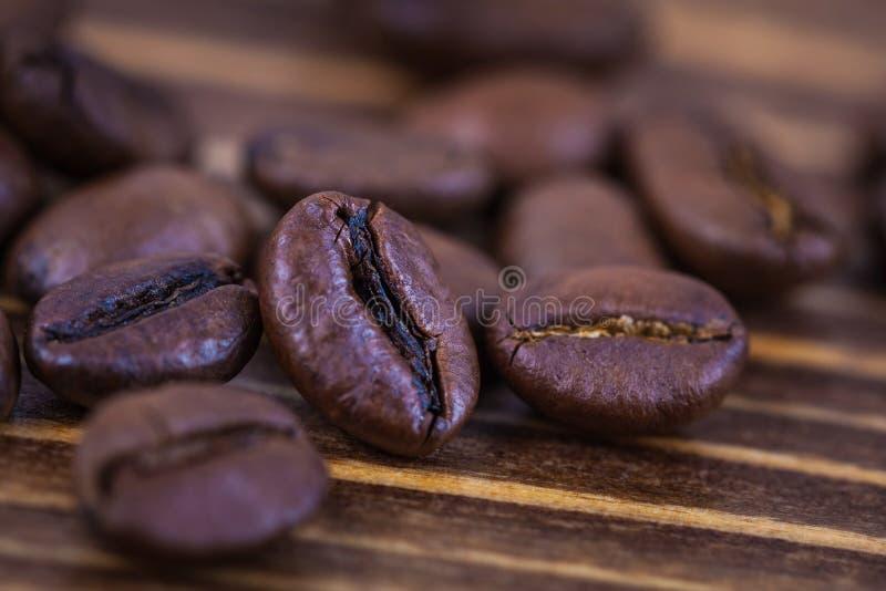 Piec kawowi beens na drewnianym stole, zakończenie w górę zdjęcia royalty free