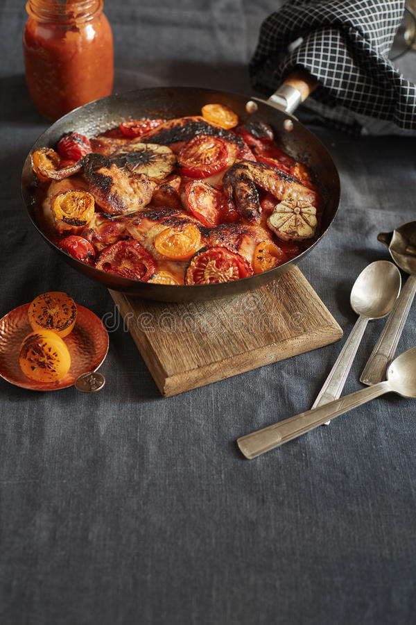 Piec kurczak rozdziela z pomidorami i czosnkiem w niecce obraz stock