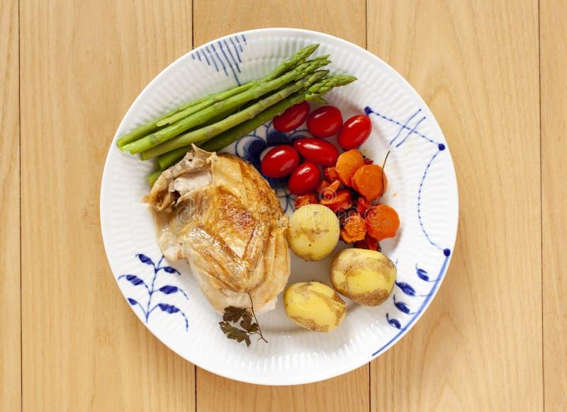 Piec kurczak z śliwkowymi pomidorami, nowymi grulami i zielonym asparagusem na talerzu, Odg?rny widok na Drewnianym tle - Wizerun zdjęcie royalty free
