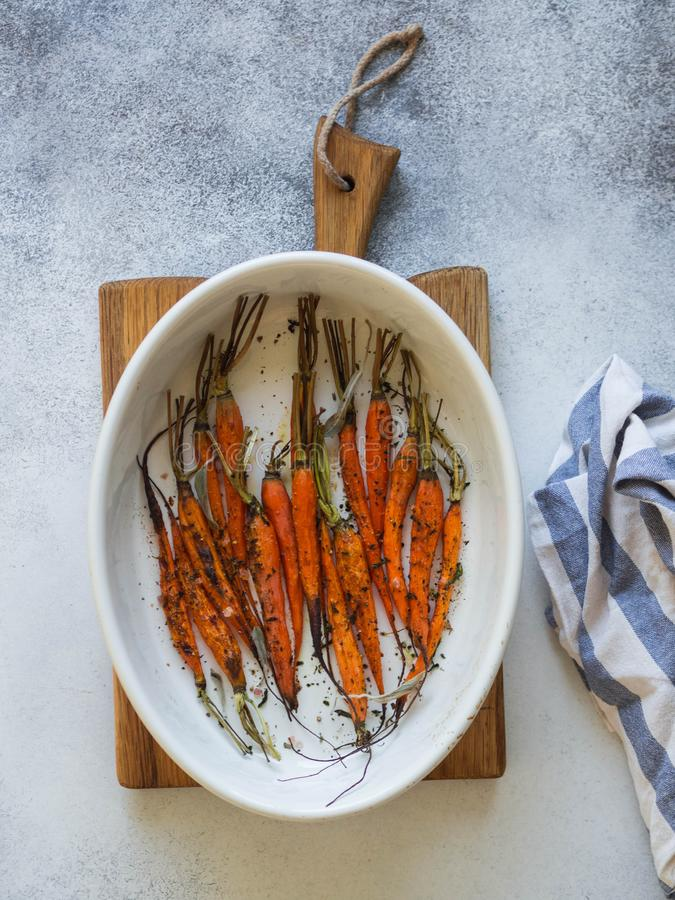 Piec młode pomarańczowe marchewki w owalnym ceramicznym pieczenia naczyniu na drewnie wsiadają zdjęcie royalty free