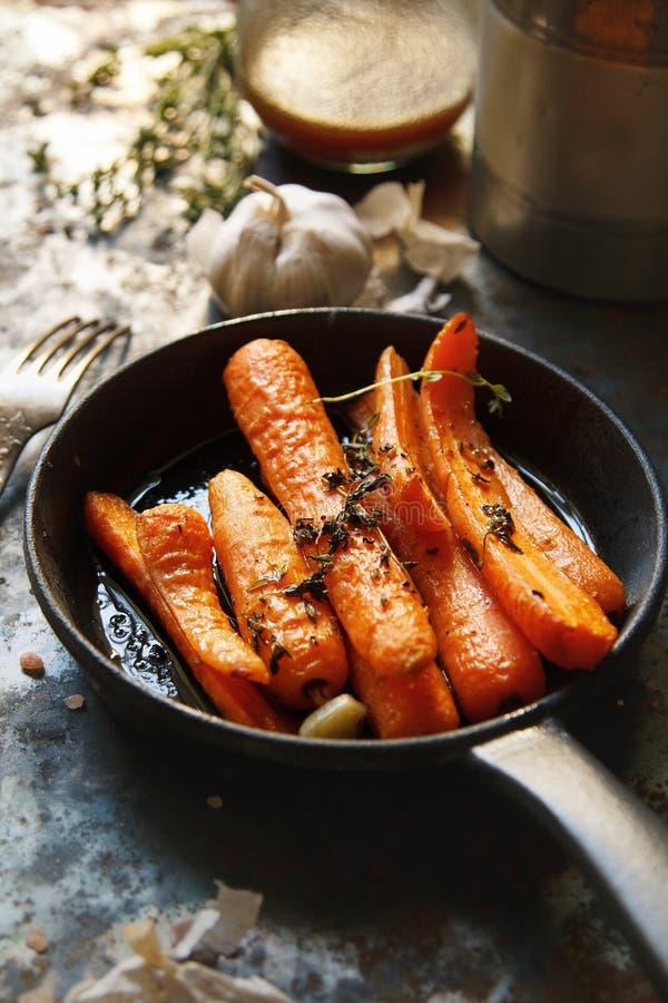 Piec marchewki z ciężką smaży niecką na nieociosanym tle obraz stock