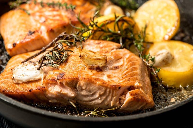 Piec na grillu łosoś ryba z ziele, czosnkiem i cytryną, fotografia royalty free