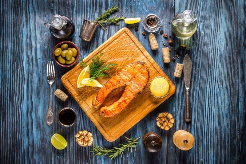 Piec na grillu łososiowy stek z cytryną na nieociosanym drewnianym tle obrazy royalty free