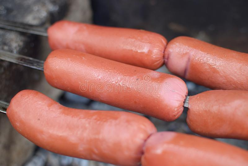 Piec na grillu świeże kiełbasy nad węglami smakowitymi na skewer fotografia stock