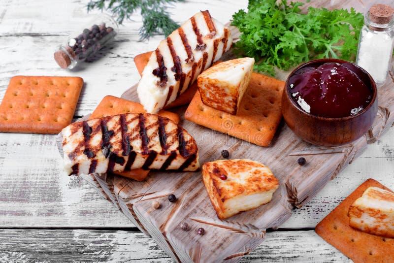 Piec na grillu adyghe ser, krakersy, czerwony dżem, pikantność i cress sałatka na drewnianej desce, zdjęcie royalty free