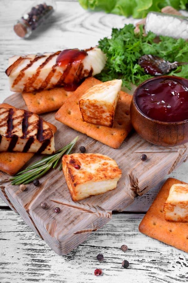 Piec na grillu adyghe ser, krakersy, czerwony dżem, pikantność i cress sałatka na drewnianej desce, obraz royalty free
