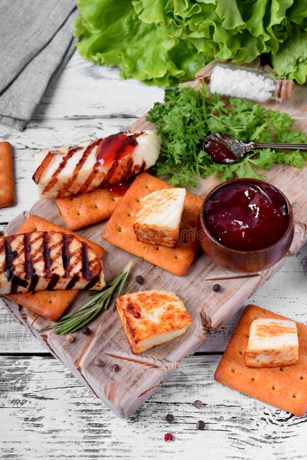 Piec na grillu adyghe ser, krakersy, czerwony dżem, pikantność i cress sałatka na drewnianej desce, obraz stock