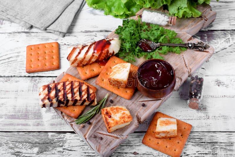 Piec na grillu adyghe ser, krakersy, czerwony dżem, pikantność i cress sałatka na drewnianej desce, obrazy stock
