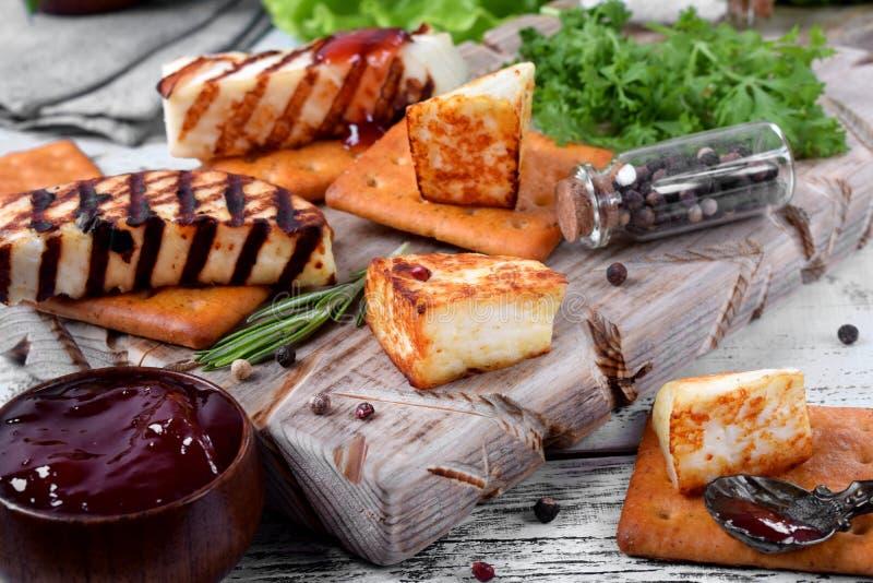 Piec na grillu adyghe ser, krakersy, czerwony dżem, pikantność i cress sałatka na drewnianej desce, fotografia royalty free
