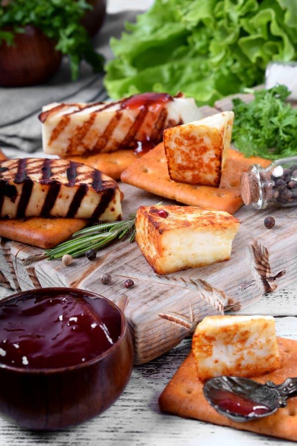 Piec na grillu adyghe ser, krakersy, czerwony dżem, pikantność i cress sałatka na drewnianej desce, obrazy royalty free