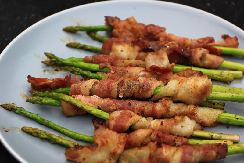 Piec na grillu bekon zawijał zielonego asparagus na ciemnym tle fotografia stock