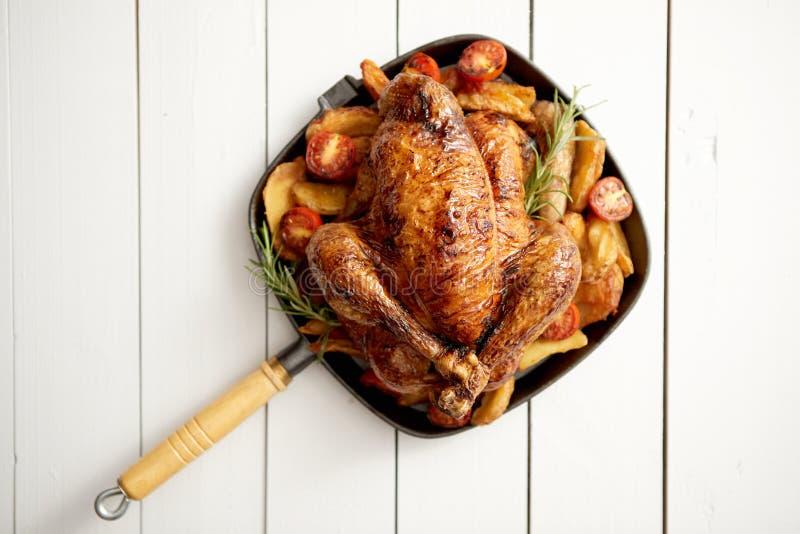 Piec na grillu cały kurczak w obsady żelaza czerni niecce z grulami, pomidorami i rozmarynami, obrazy stock