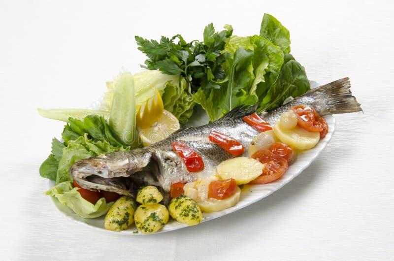 Piec na grillu denny bas z warzywami na talerzu na białym tle obrazy stock