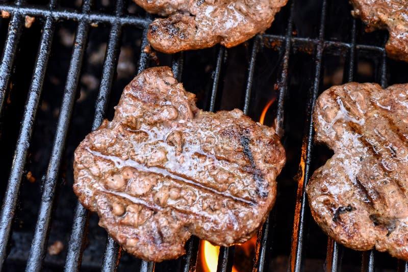 Piec na grillu domowej roboty hamburgery na grilla zbli?eniu obrazy stock