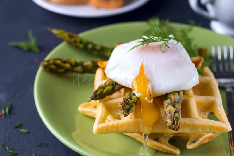 Piec na grillu gofr z Zielonym gotowanym asparagusem z Kłusującym jajkiem z solą i pikantność na ceramicznym talerzu jako zdrowy, obraz royalty free