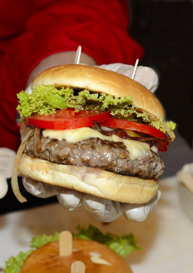 Piec na grillu hamburger pokazuje od ludzkiej ręki zdjęcie stock