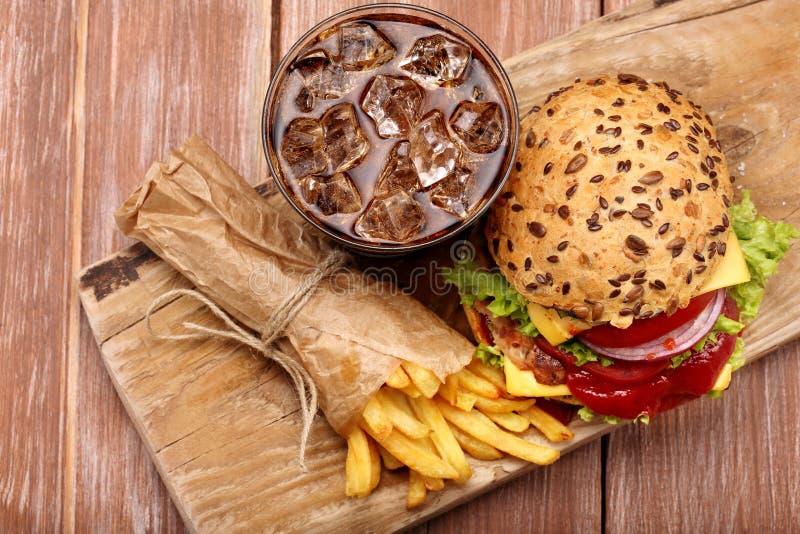 Piec na grillu hamburger z dłoniakami i kolą na drewnianym tle fotografia stock