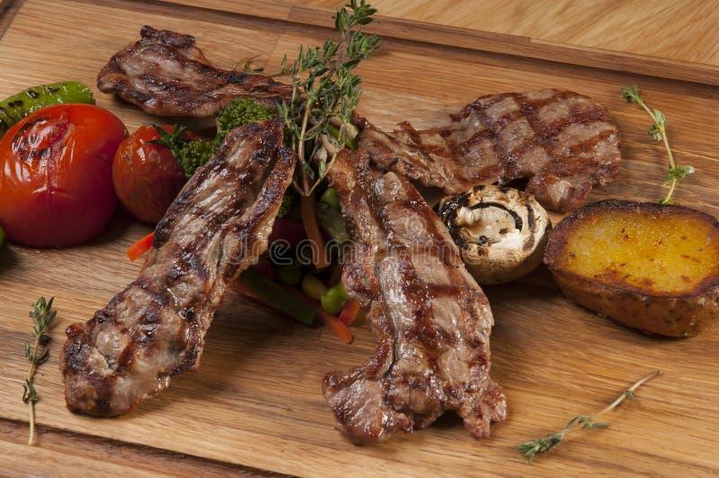 Piec na grillu jagnięcy kotleciki na drewnianej porci desce zdjęcie stock