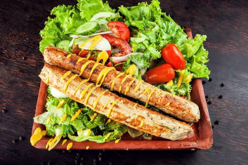 Piec na grillu kiełbasa z warzywami i musztardą na drewnianej desce obraz royalty free