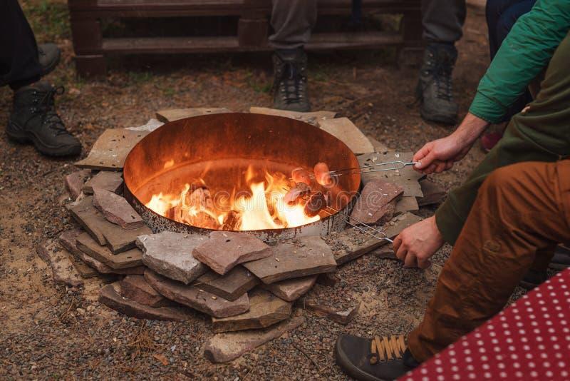 Piec na grillu kiełbasy nad ogniskiem, obozowicze piec kiełbasy na wznosić toast rozwidlają Pożarniczy miejsce, przyjaciele, tury zdjęcie stock
