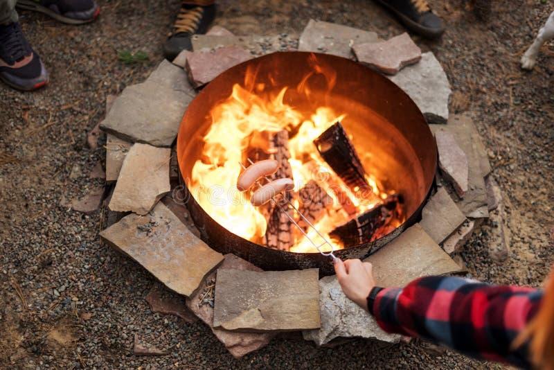 Piec na grillu kiełbasy nad ogniskiem, obozowicze piec kiełbasy na wznosić toast rozwidlają Pożarniczy miejsce, przyjaciele, tury zdjęcia stock