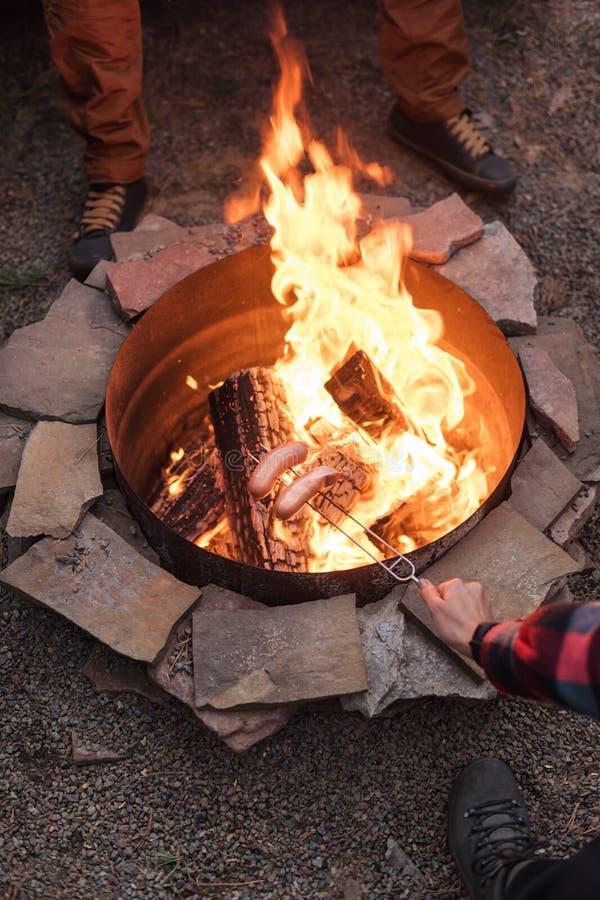 Piec na grillu kiełbasy nad ogniskiem, obozowicze piec kiełbasy na wznosić toast rozwidlają Pożarniczy miejsce, przyjaciele, tury fotografia stock
