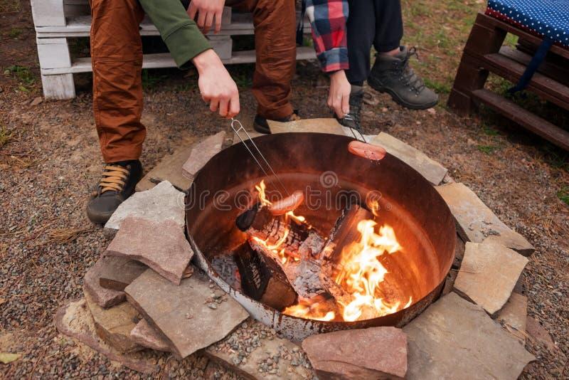 Piec na grillu kiełbasy nad ogniskiem, obozowicze piec kiełbasy na wznosić toast rozwidlają Pożarniczy miejsce, przyjaciele, tury obraz royalty free